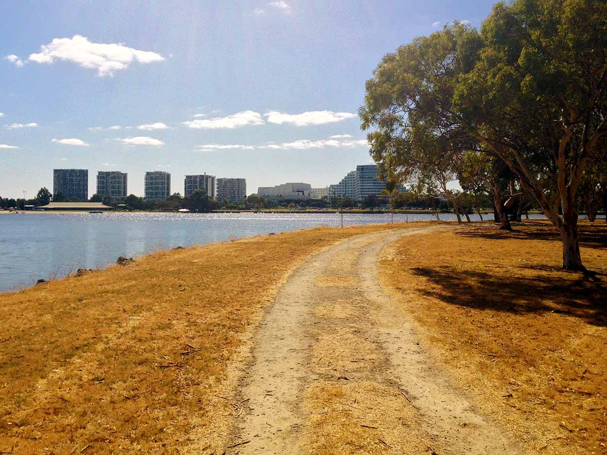 A dusty road on the eastly end of Heirisson Island with the Perth Crown entertainment precinct in the distance, Perth, Western Australia