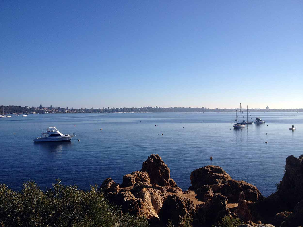 Boats moored near the rocky cliffs of Point Walter Reserve, Swan River, Perth, Western Australia