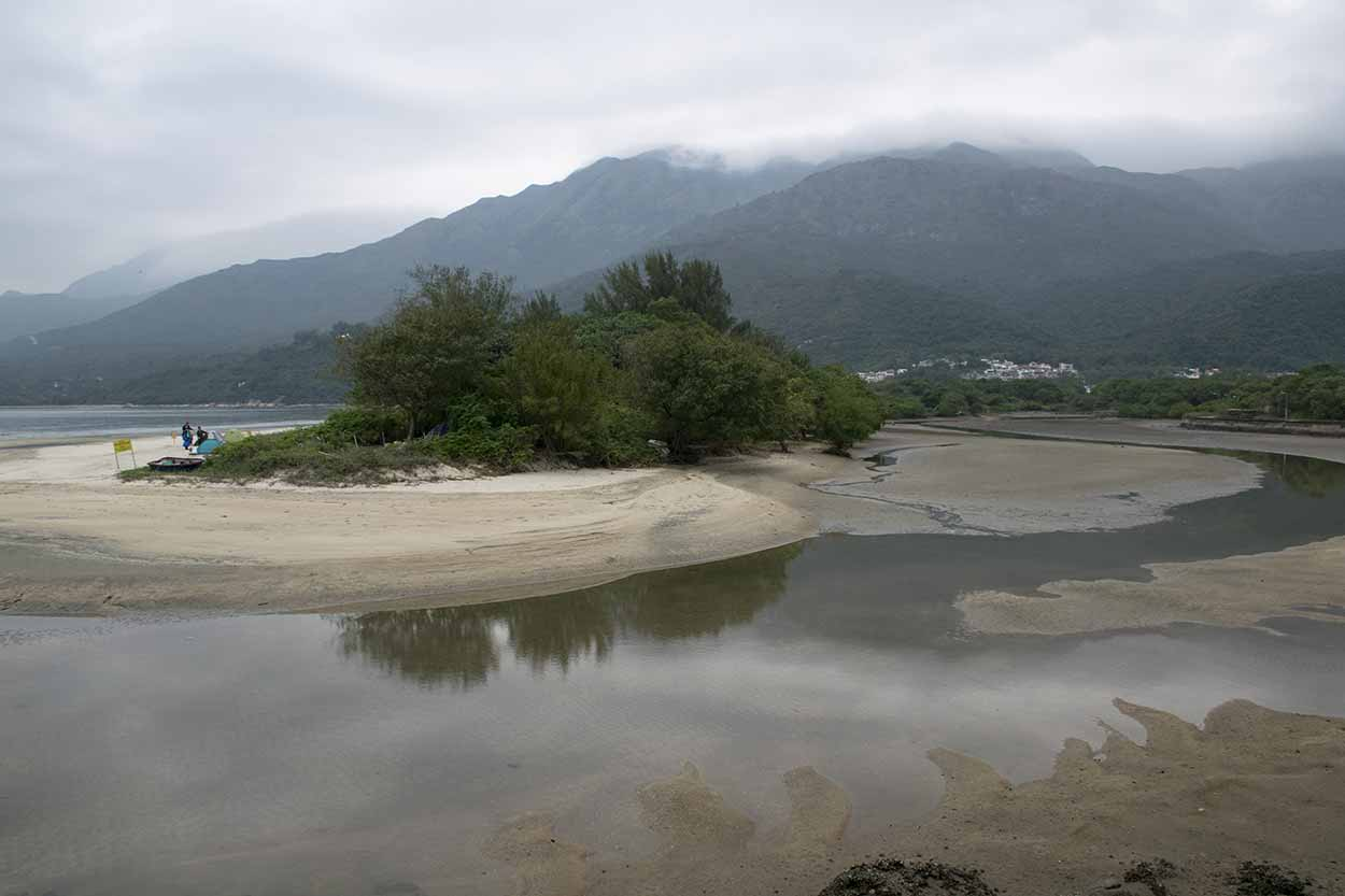 Misty Lantau peaks over Pui O beach, Lantau Island, Hong Kong, China
